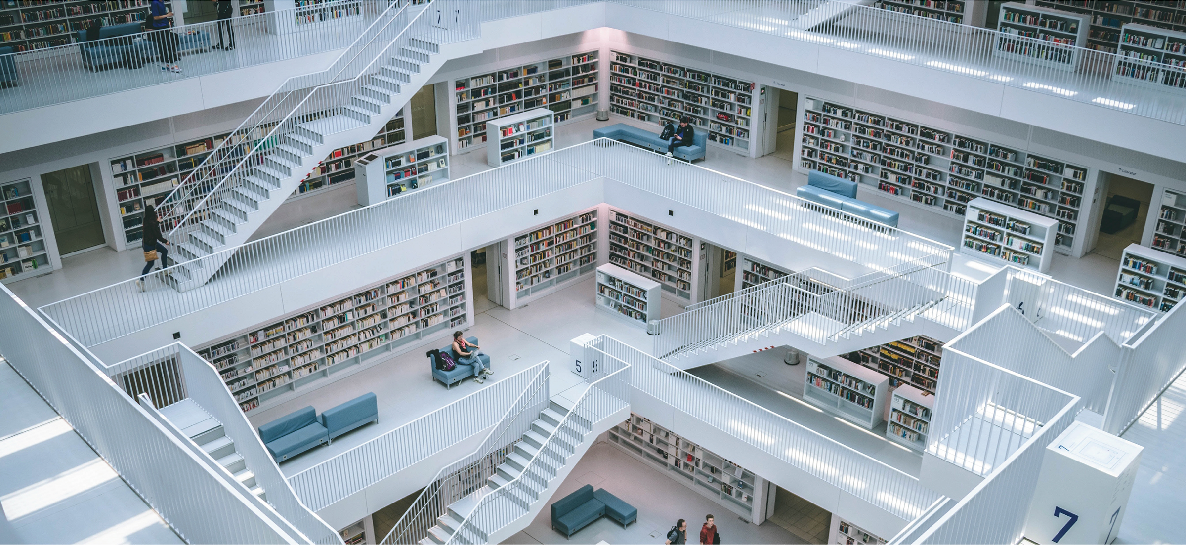 Staircases and book shelves with some people sitting down or walking