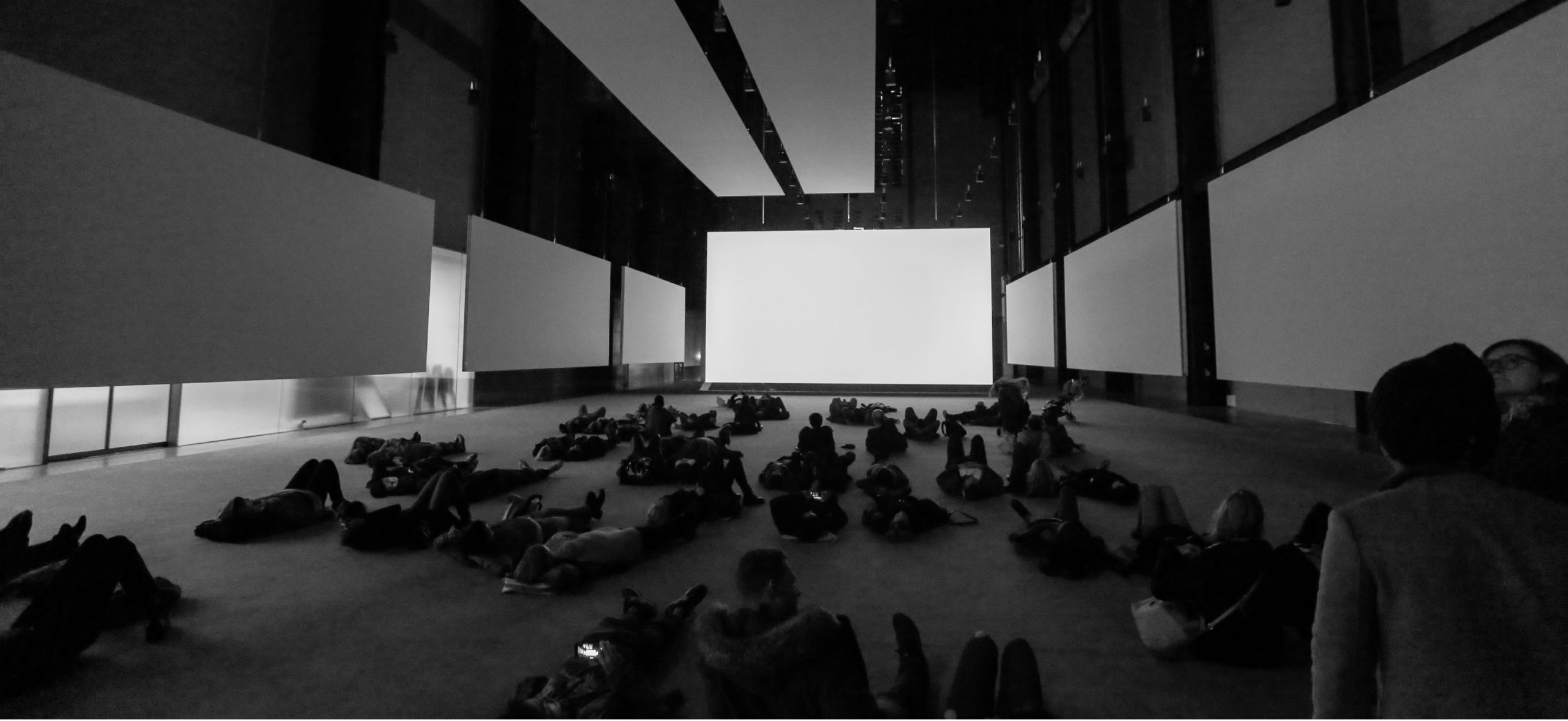 Group of people lying down in a room before a massive blank screen