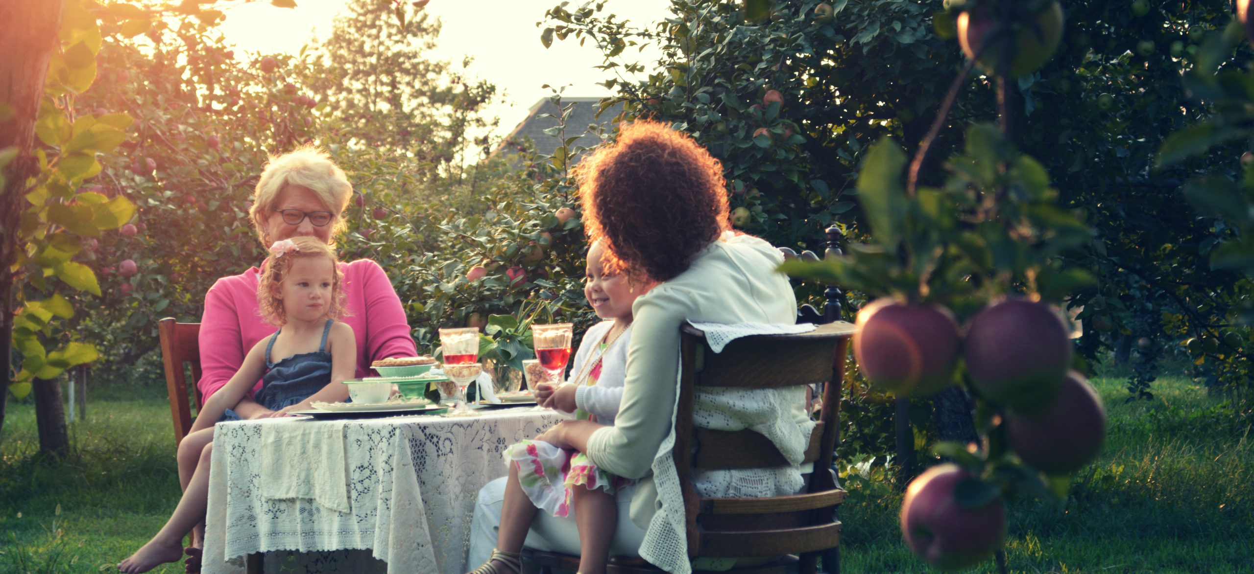 Two women with children on their lap dining in an orchard