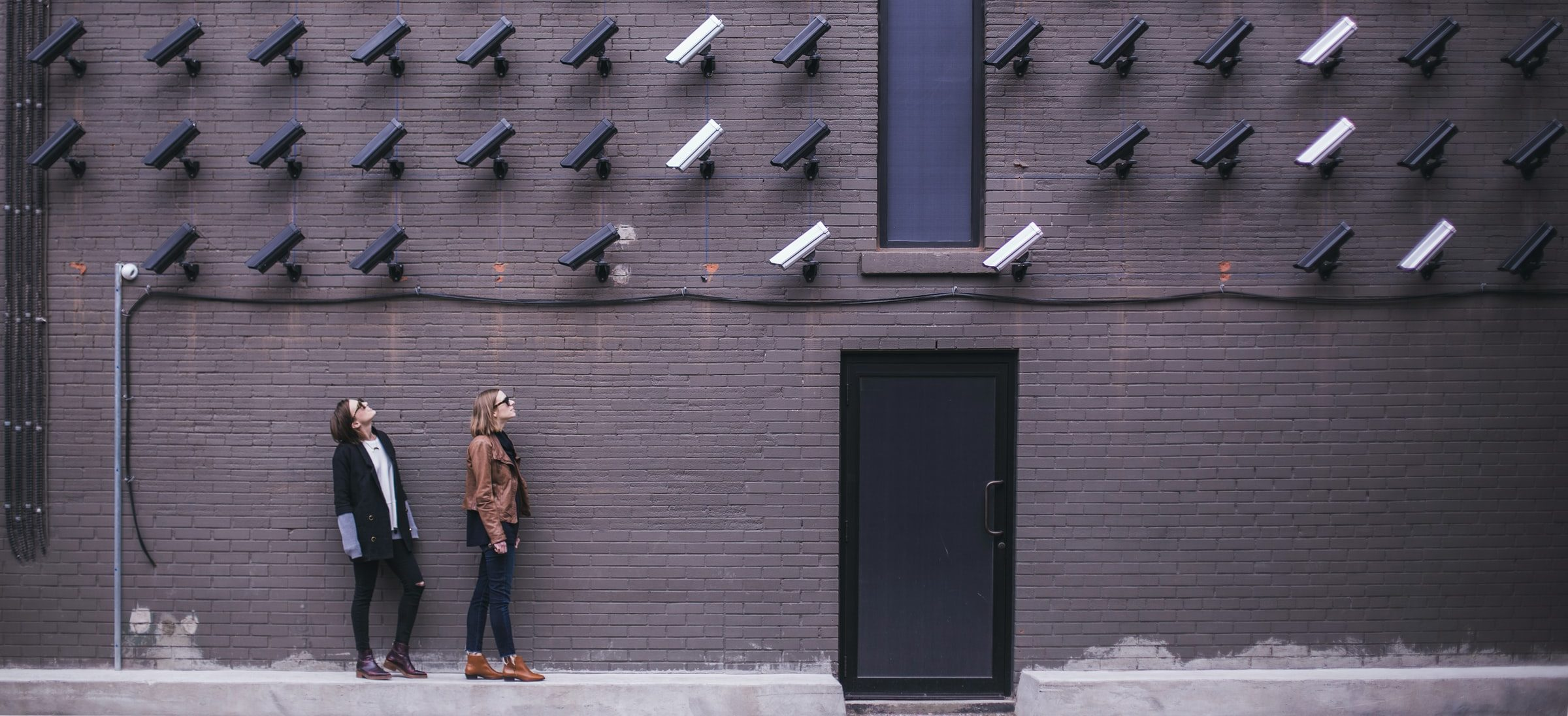 Women looking at a bank of security cameras