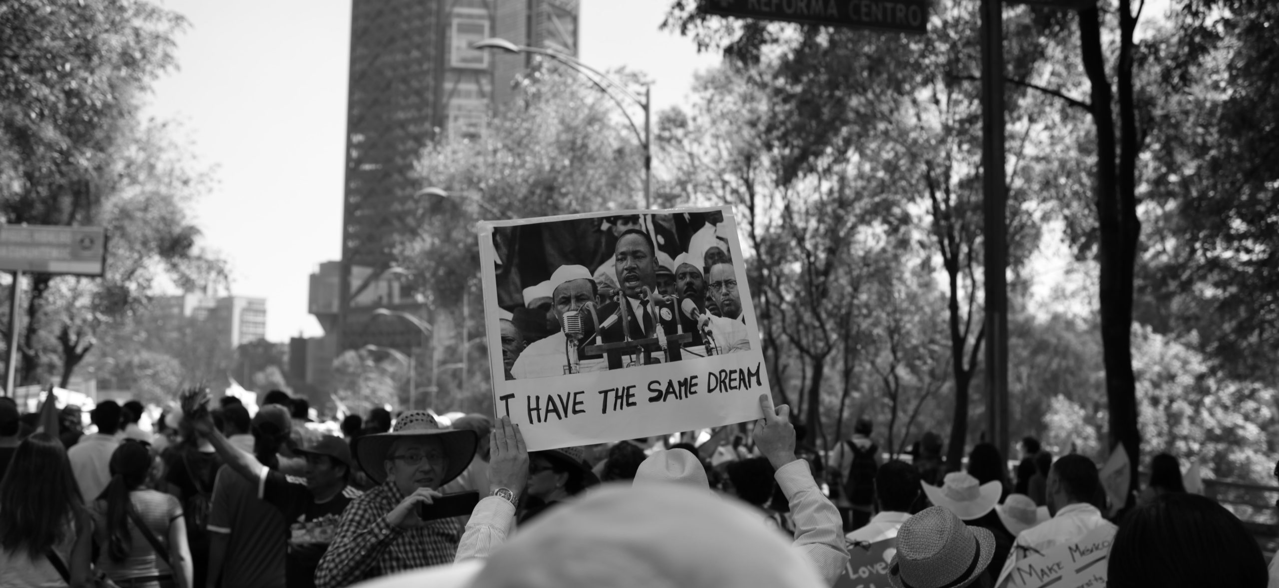 People at a protest with someone holding a Martin Luther King picture with I have the same dream quoted underneath