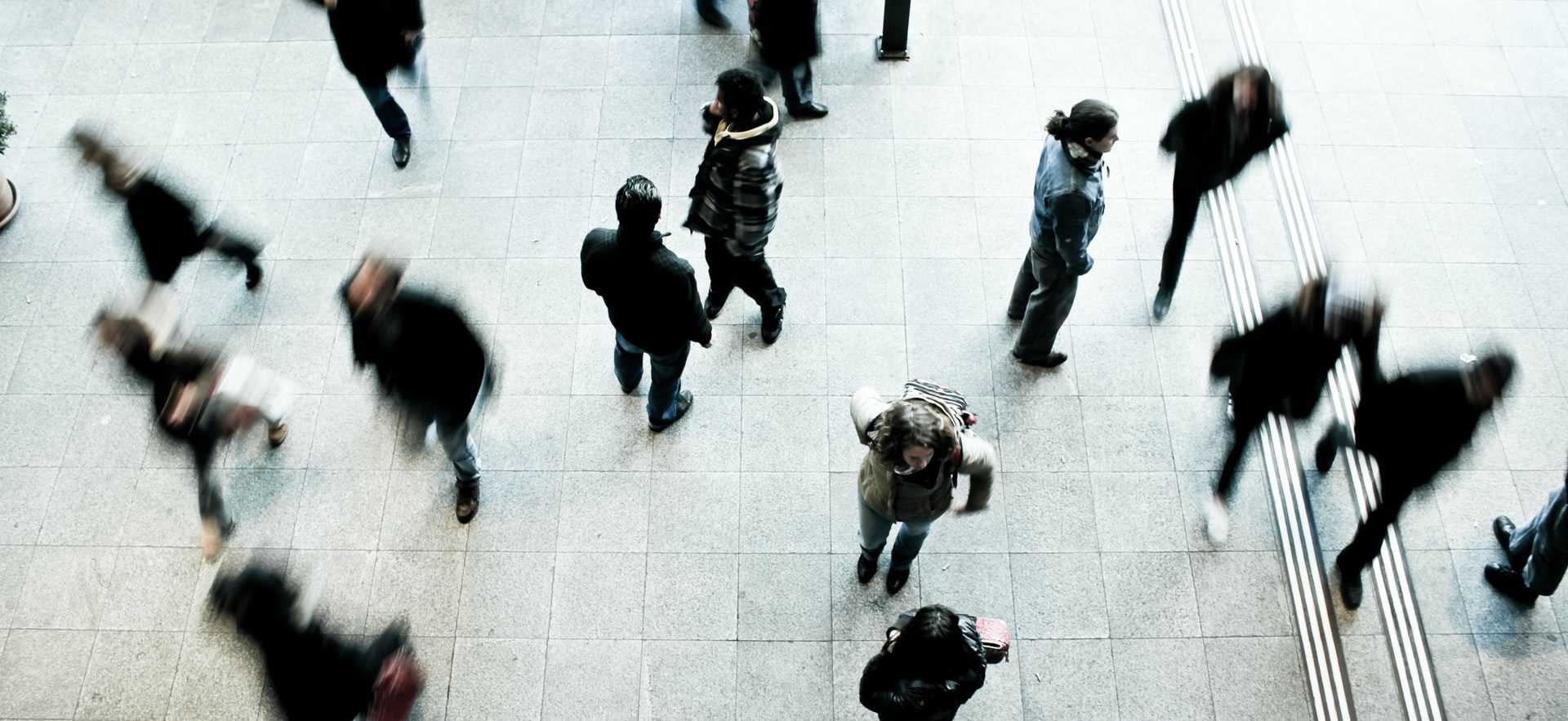 People in an open concourse commuting