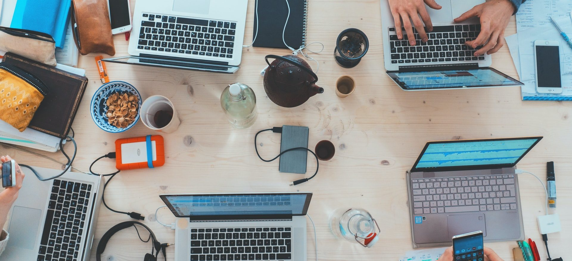 Laptops, hard drives and tea, people working on a shared table. Photo by Marvin Meyer on Unsplash
